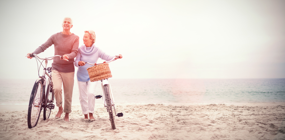 Elderly couple walking along the beach with bikes