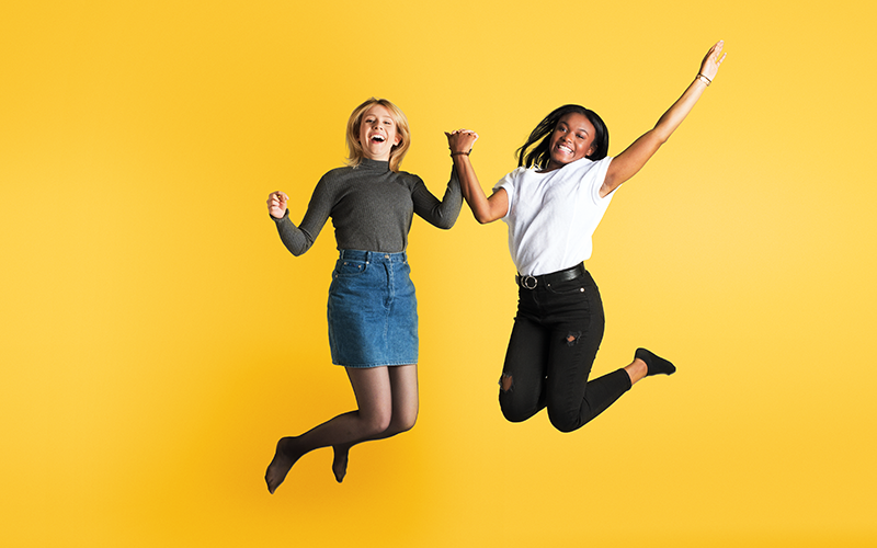 Two young women jumping in the air