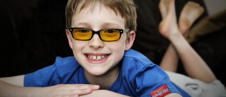 A little boy in glasses smiles to the camera.