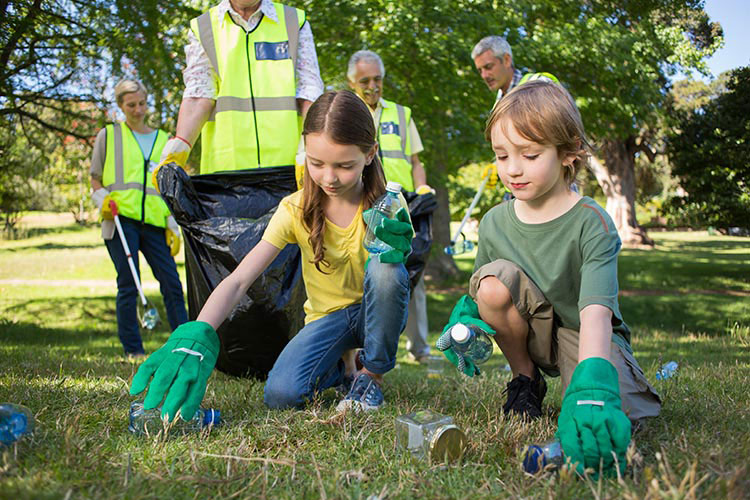Two children wearing green gloves, picking up rubbish in a park.